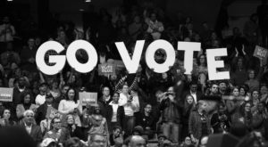 "Group of people hold up a ""Go Vote"" sign during a get-out-the-vote rally"