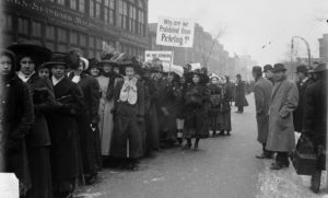 Image of a parade of women during the garment workers' strike in Chicago, Illinois. Some women are carrying signs, and one sign reads: Why are we prohibited from picketing? This parade took place on Dec. 12, 1910, during United Garment Workers of America strike.